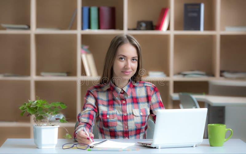Lavoro professionale delle giovani free lance femminili allo scrittorio nell'interno caldo fotografie stock libere da diritti