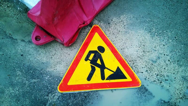 Lavoro stradale triangolare del segnale stradale che mette sulla terra fotografia stock libera da diritti