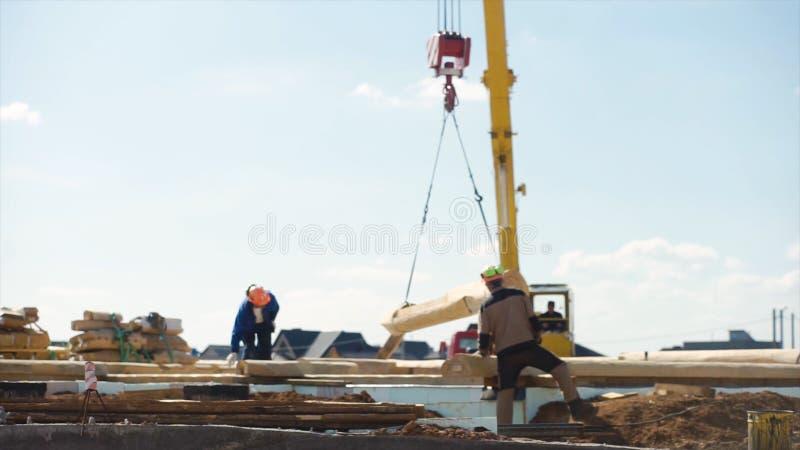 Lavoro sul cantiere nella sfuocatura per i precedenti clip Due costruttori in un casco sul cantiere fotografia stock libera da diritti
