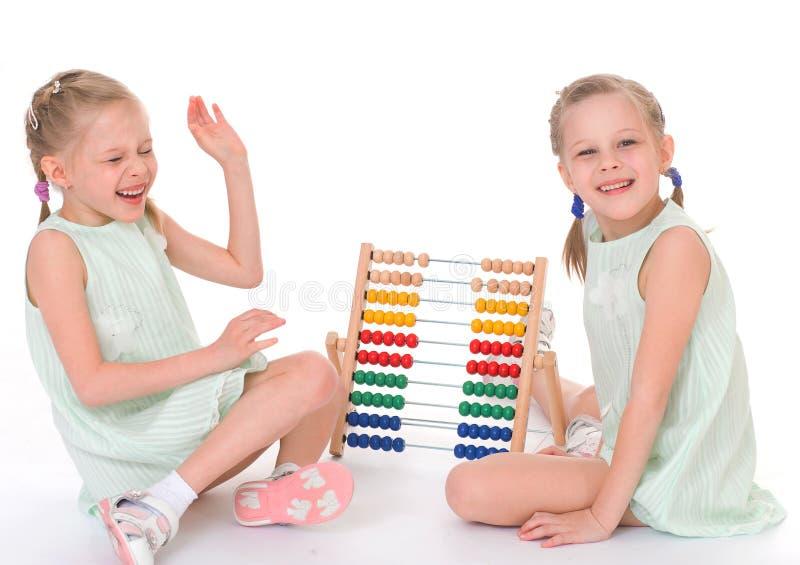 Lavoro sveglio delle sorelle nell'ambiente di Montessori. immagine stock