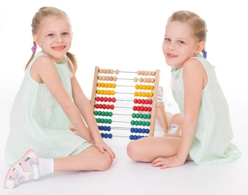 Lavoro sveglio delle sorelle nell'ambiente di Montessori. fotografia stock libera da diritti