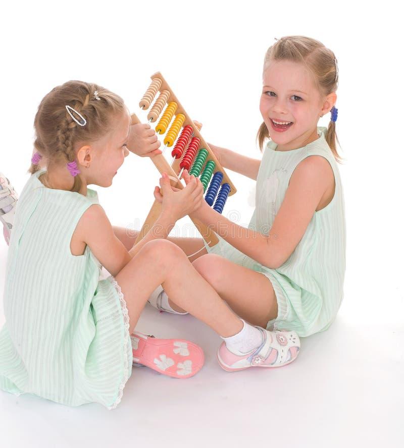 Lavoro sveglio delle sorelle nell'ambiente di Montessori. immagine stock libera da diritti