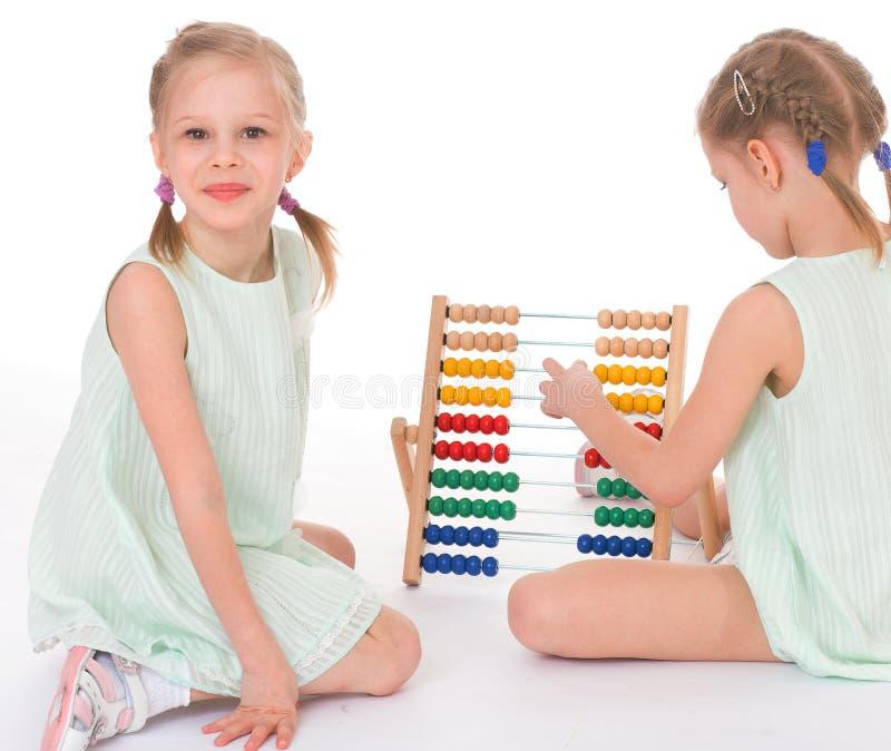 Lavoro sveglio delle sorelle nell'ambiente di Montessori. immagini stock libere da diritti