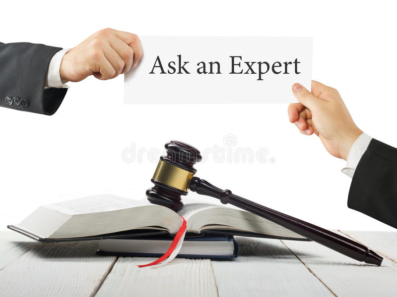 Law book and wooden judges gavel on table in a courtroom or law enforcement office. Lawyer Hands holding business card. With text Ask an Expert stock photo
