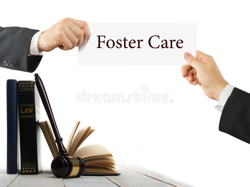 Law book and wooden judges gavel on table in a courtroom or law enforcement office. Lawyer Hands holding business card. With text Foster Care royalty free stock photography