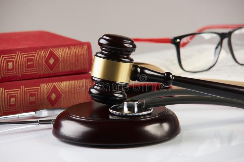 Law books with wooden judges gavel and medical stethoscope royalty free stock photo