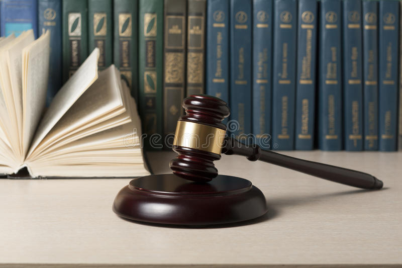Law concept - Book with wooden judges gavel on table in a courtroom or enforcement office. stock photos