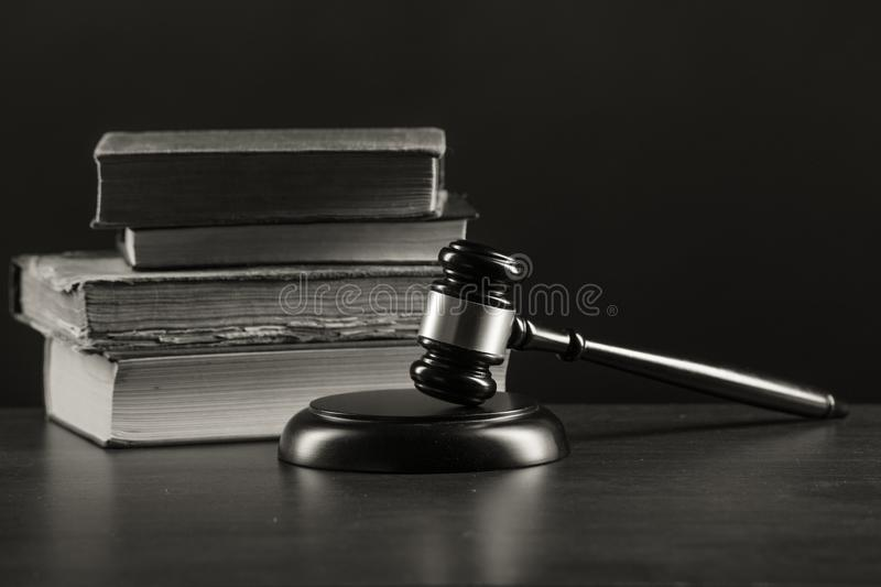 Law concept - Open law book with a wooden judges gavel on table in a royalty free stock photos
