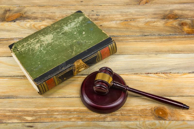Law concept - Open law book with a wooden judges gavel on table in a courtroom or law enforcement office isolated on. Law concept - Open law book with a wooden royalty free stock photos