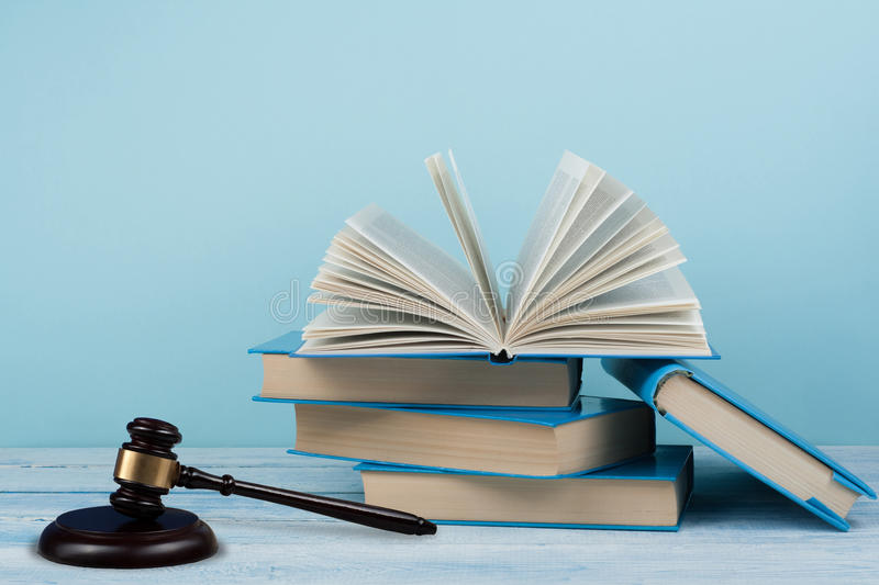 Law concept open book with wooden judges gavel on table in a courtroom or law enforcement office, blue background. Copy. Space for text stock photo