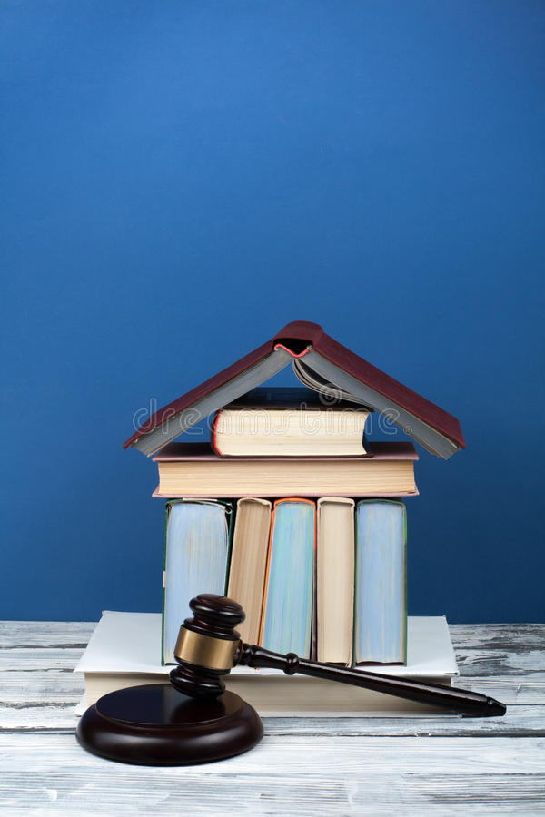 Law concept open book with wooden judges gavel on table in a courtroom or law enforcement office, blue background. Copy. Space for text royalty free stock photos