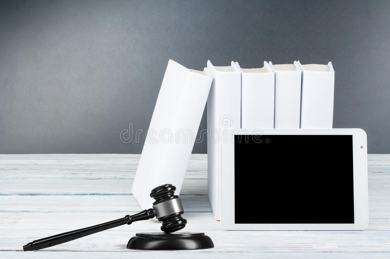 Law concept - Open law book with a wooden judges gavel on table in a courtroom or law enforcement office on royalty free stock image