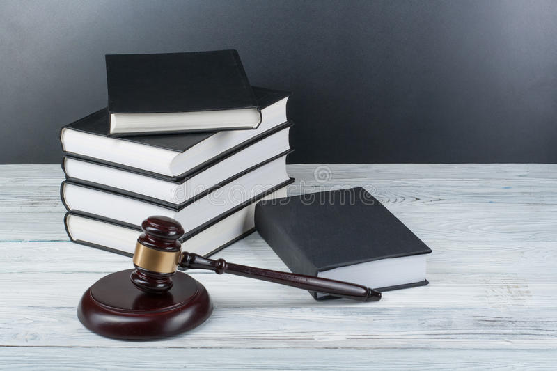 Law concept - Open law book with a wooden judges gavel on table in a courtroom or law enforcement office isolated on. Law concept - Open law book with a wooden royalty free stock images