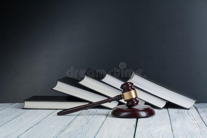 Law concept - Open law book with a wooden judges gavel on table in a courtroom or law enforcement office on. Blue background. Copy space for text stock image