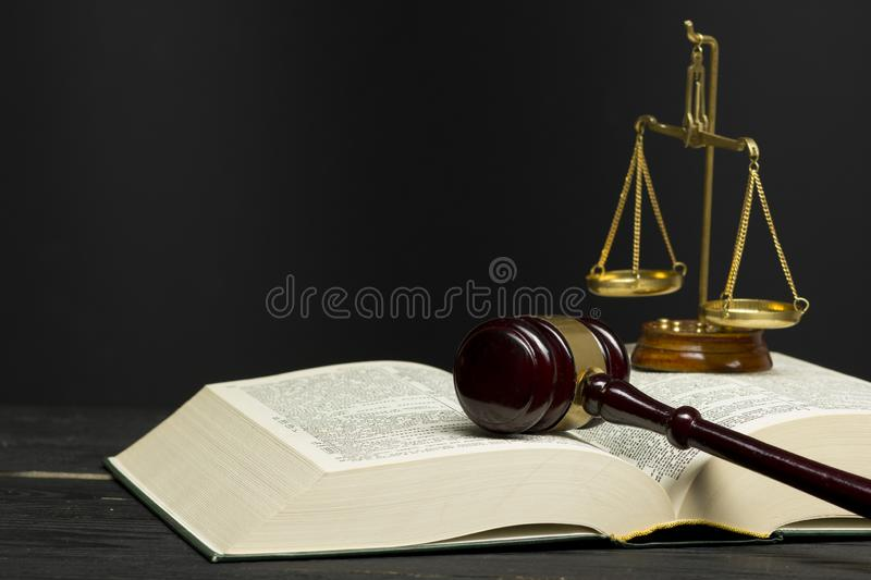 Law concept - Open law book with a wooden judges gavel on table in a courtroom or law enforcement office royalty free stock images