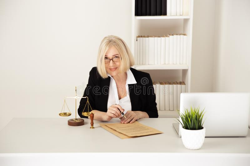 Law concept. Woman in glasses working with notarized paper. royalty free stock photography