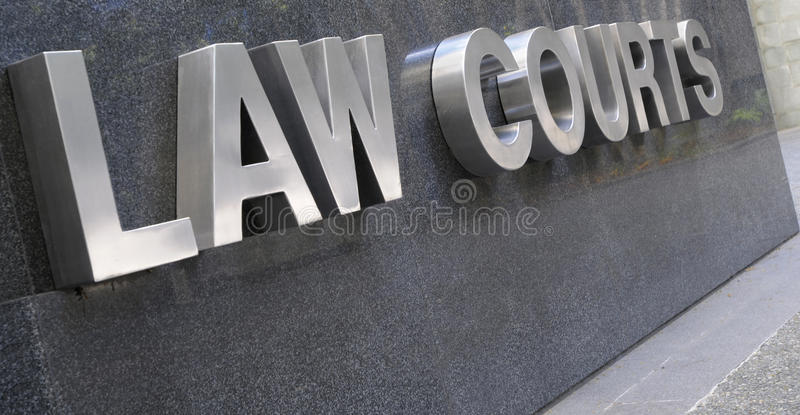 Law Courts sign in stainless steel, courthouse building. Law Courts sign in stainless steel against black marble royalty free stock photography