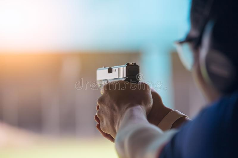 Law enforcement aim pistol by two hand in academy shooting range. In flare and vintage color stock photo