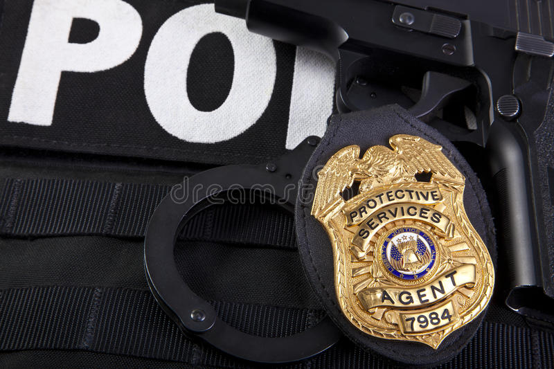 Law enforcement badge with gun, handcuffs and bullets royalty free stock photos