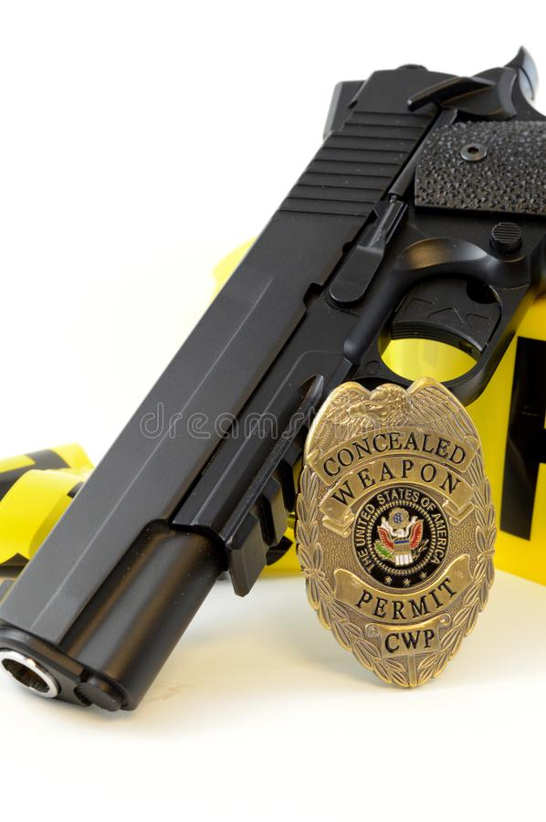 Law Enforcement Concept. Closeup view of a handgun with a weapons badge and some police tape for law enforcement royalty free stock images