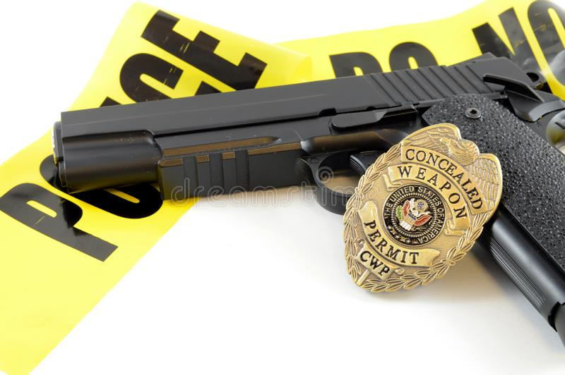 Law Enforcement Concept. Closeup view of a handgun with a weapons badge and some police tape for law enforcement stock images