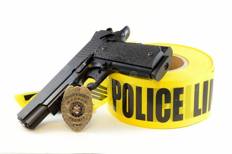 Law Enforcement Concept. Closeup view of a handgun with a weapons badge and some police tape for law enforcement royalty free stock photography