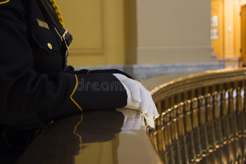 Law enforcement officer in dress uniform. Female law enforcement officer in dress uniform resting gloved hands on brass rail at state capitol building. Image royalty free stock photography