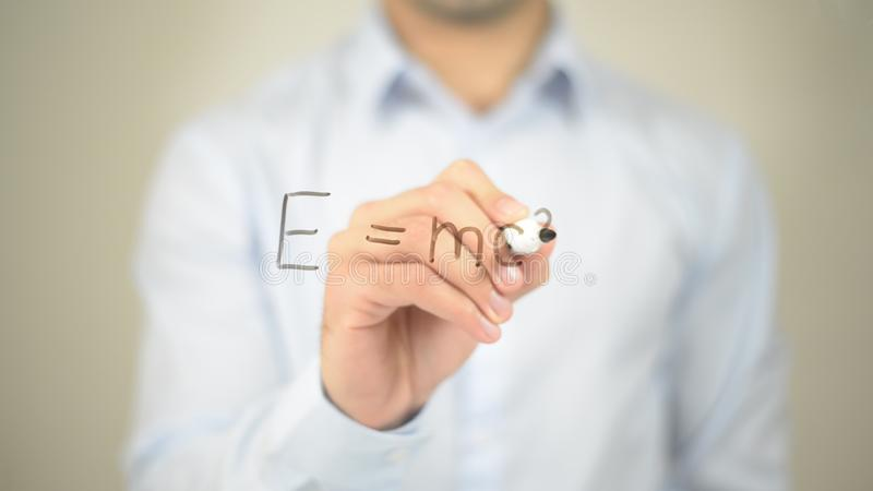 Law of Equivalence of Energy and Mass, Man writing on transparent screen royalty free stock photo