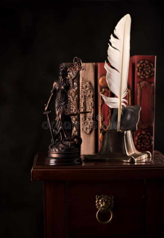 Statue Justice Inkwell with feather and books. Law and justice concept. Statue Justice Inkwell with feather and books royalty free stock image