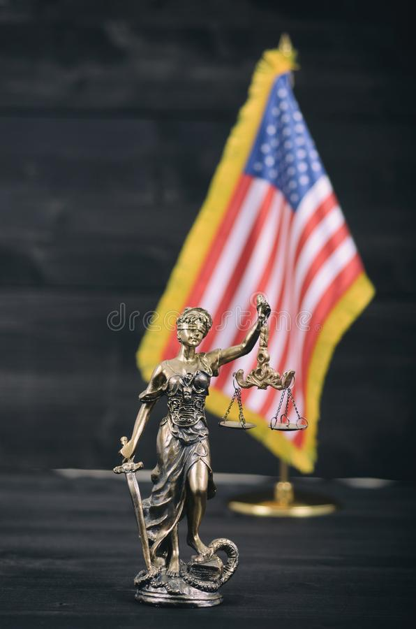 Scales of Justice, Justitia, Lady Justice in front of the American flag in the background royalty free stock photo