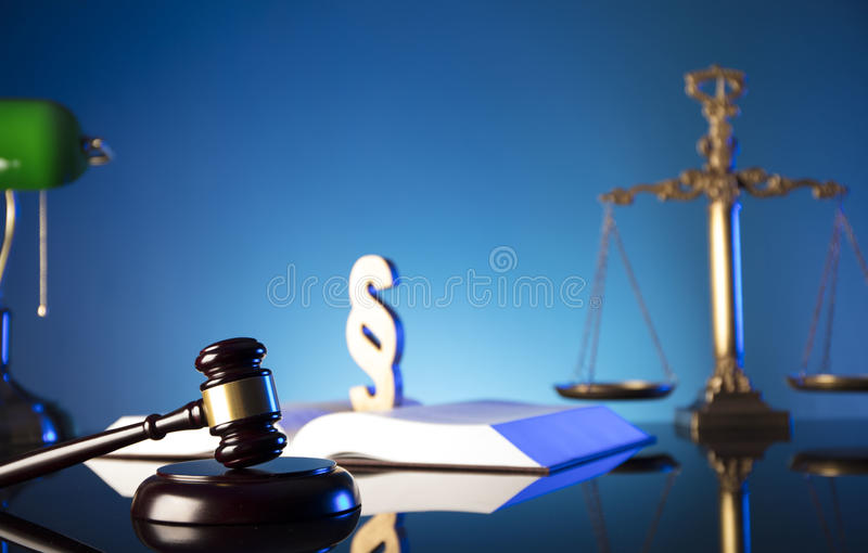 Law theme and concept. Lawyer, counselor office. Consultation with a lawyer concept. Gavel and scale of justice on glass table and blue background royalty free stock photo