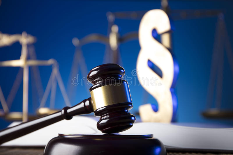 Law theme and concept. Lawyer, counselor office. Consultation with a lawyer concept. Gavel and scale of justice on old wooden table and blue background stock photo