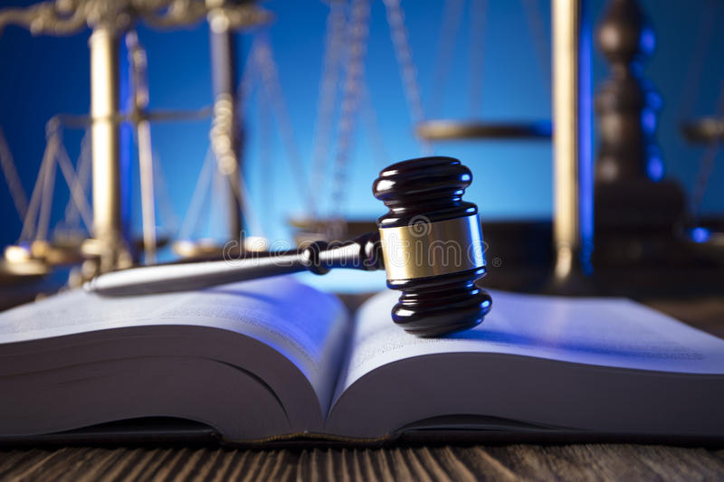 Law theme and concept. Lawyer, counselor office. Consultation with a lawyer concept. Gavel and scale of justice on old wooden table and blue background stock image