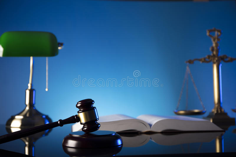 Law theme and concept. Lawyer, counselor office. Consultation with a lawyer concept. Gavel and scale of justice on old wooden table and blue background stock photos