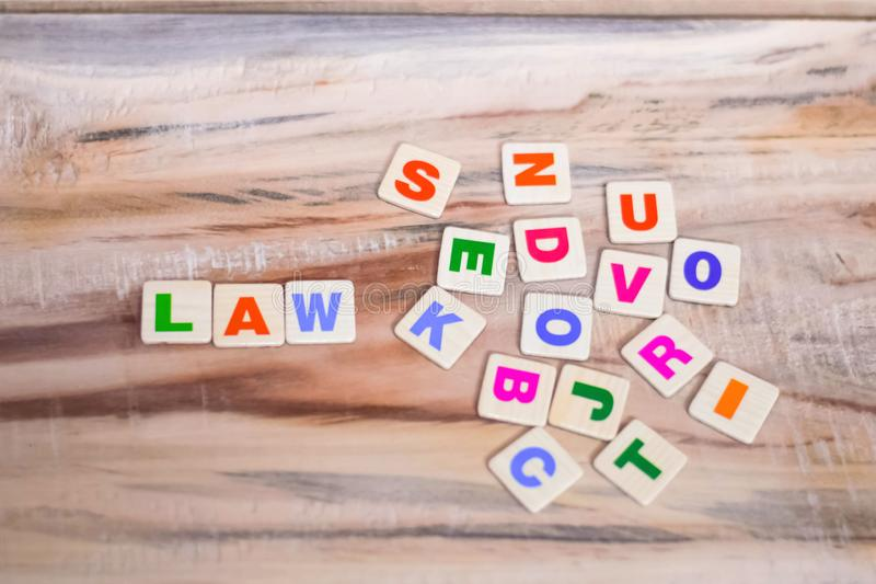 LAW WRITTEN WITH BLOCK LETTERS ON WOODEN TABLE stock photo