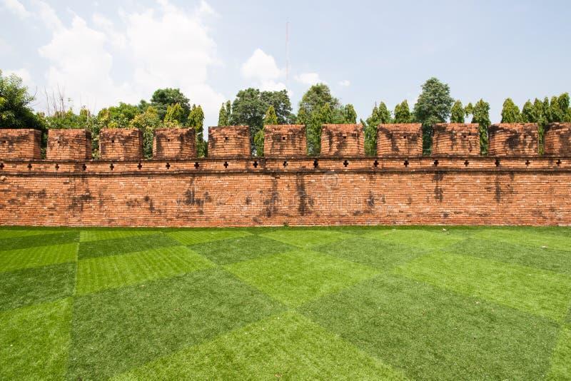 Lawn and brick wall stock photos