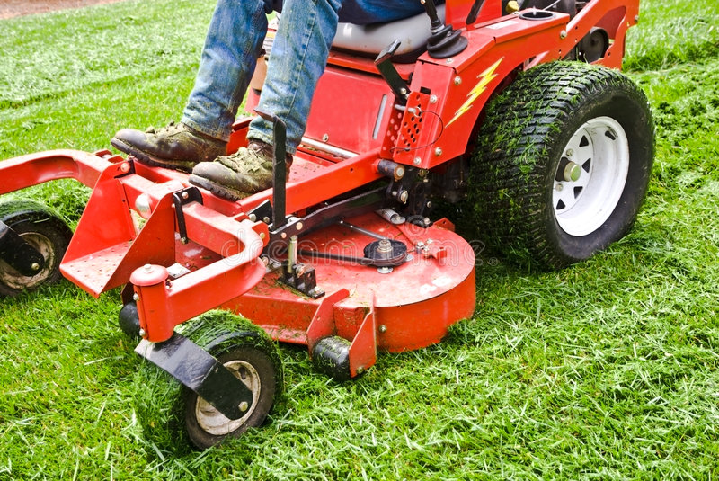 Lawn Care/ Riding Mower/ Grass. Man on a riding lawn mower that has grass stuck to the wheels. Spring and summer outdoor maintenance stock photos