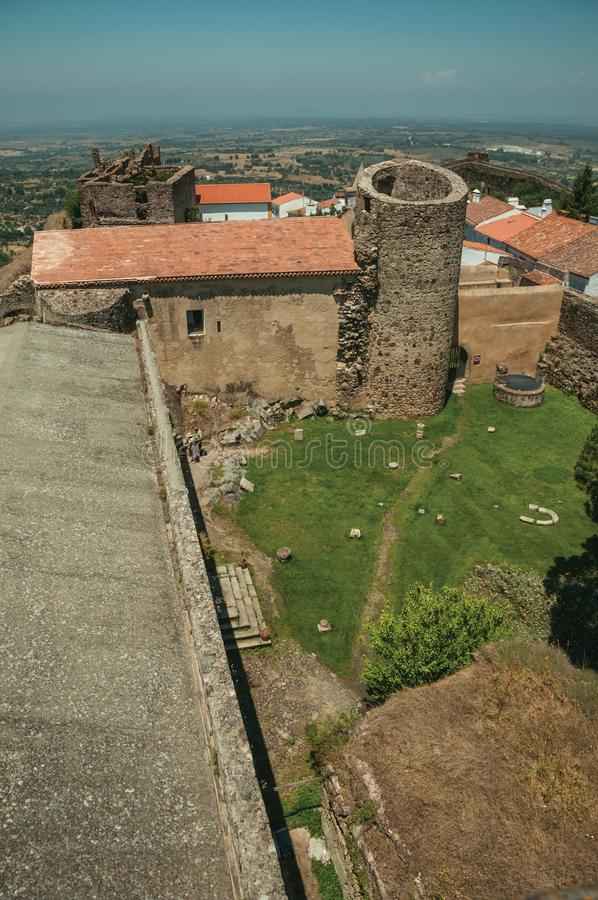 Lawn on castle central courtyard among stone walls and tower. Green lawn on castle central courtyard among stone walls and round tower, in a sunny day at Castelo stock photography