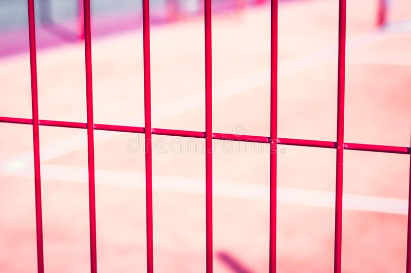 Lawn field for playing basketball behind the orange fence mesh. Metal mesh wire with tennis court. Lawn field for playing basketball behind the orange fence stock photo