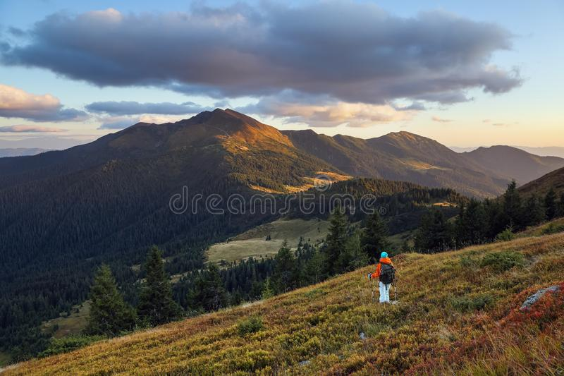 On the lawn girl stays with the back pack in the sport clothes. Landscape of the mountains. Beautiful sunset. Autumn scenery stock image