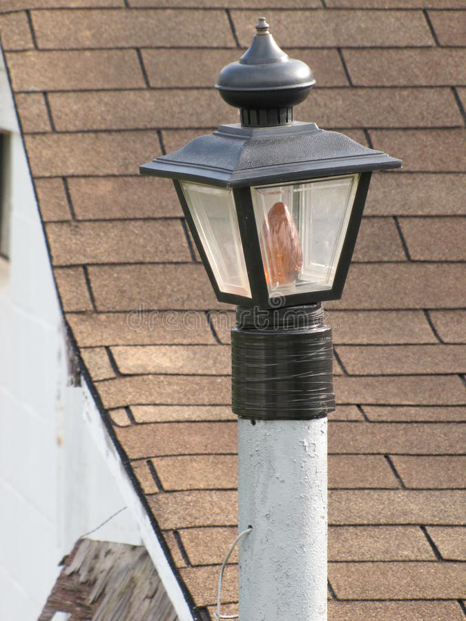 Lawn lamp post. Lawn lamp-post beckons against the pitch of the shingled roof stock photo