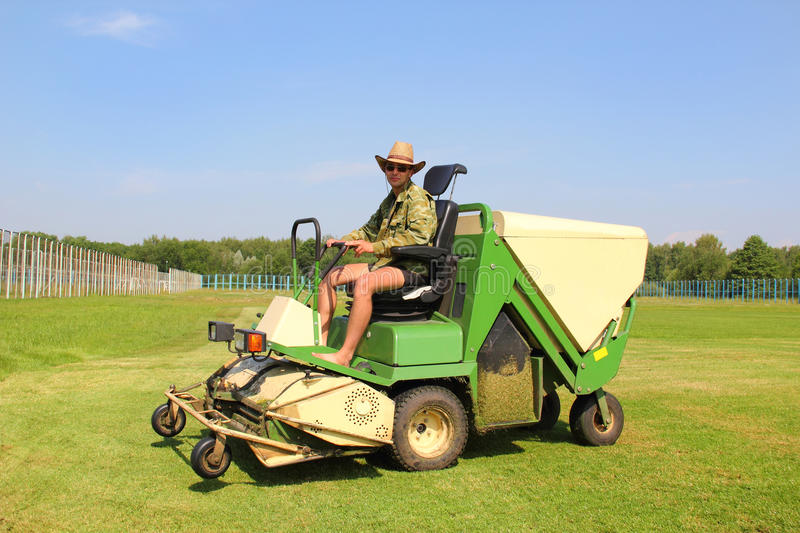 Lawn man mower. A young man mowing the grass on the play-field on a lawn mower stock image