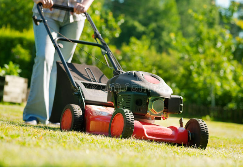 Lawn mower. Woman with lawn mower in front of back yard stock photos