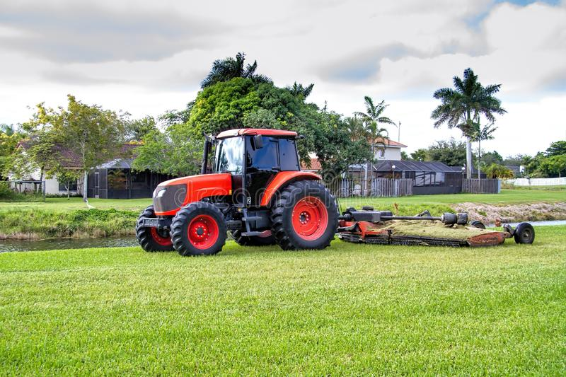 Lawn mower. Commercial tractor type lawn mower at work in a residential area royalty free stock image