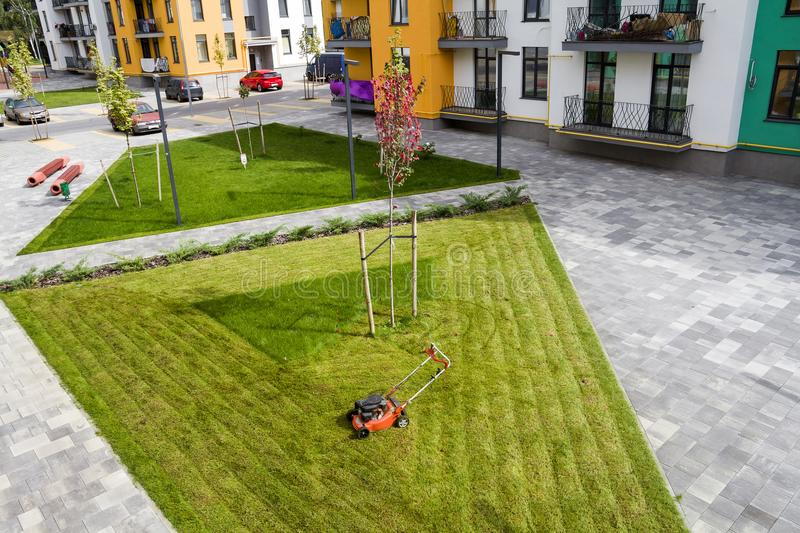 Lawn mower cutting grass on green field in yard near apartment residential building. Mowing gardener care work tool stock photos
