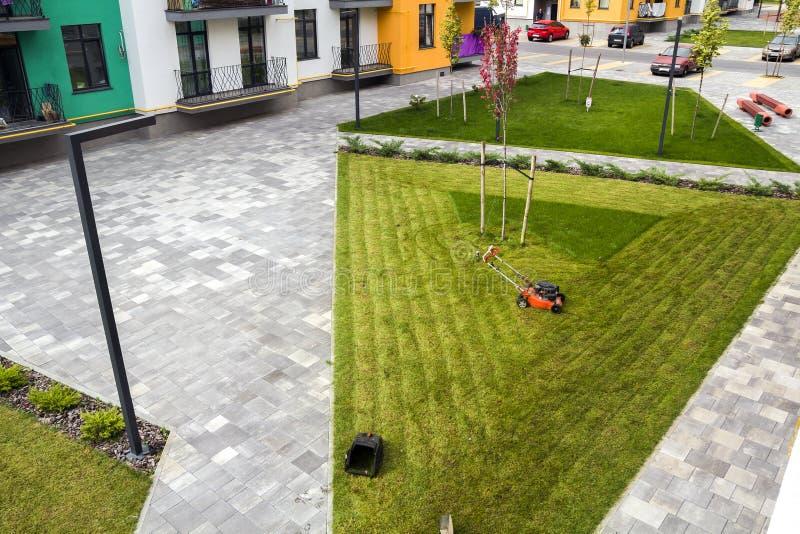 Lawn mower cutting grass on green field in yard near apartment r royalty free stock photos