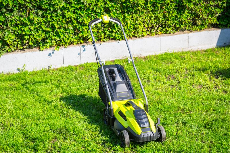 Lawn mower cutting green grass in backyard stock photo