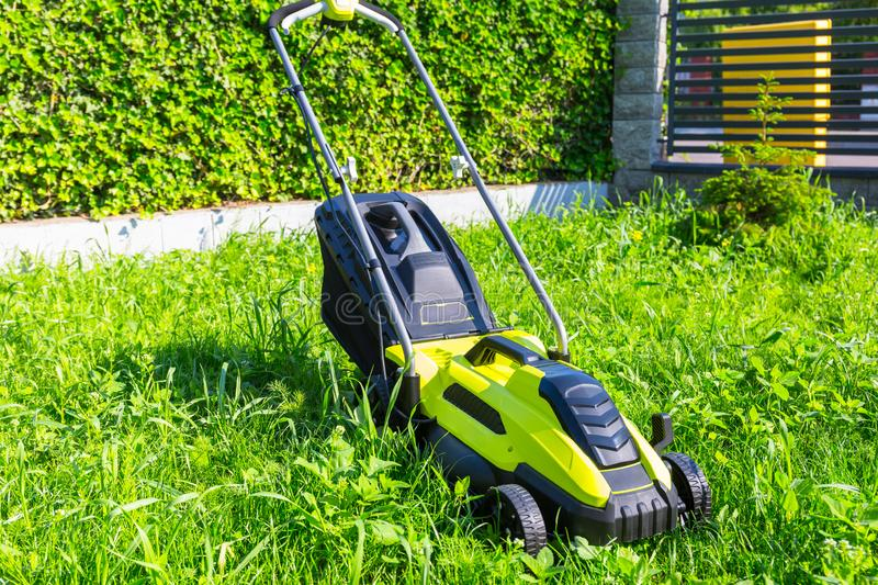 Lawn mower before cutting green grass in backyard. Care, electric, work, equipment, field, tool, gardener, nature, landscaping, service, summer, gardening stock image