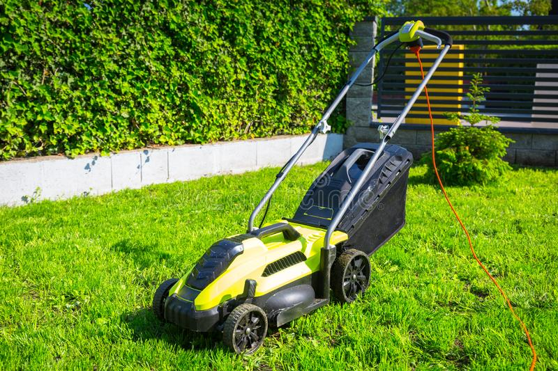 Lawn mower cutting green grass in backyard. Care, electric, work, equipment, field, tool, gardener, nature, landscaping, service, summer, gardening, sunny royalty free stock photo