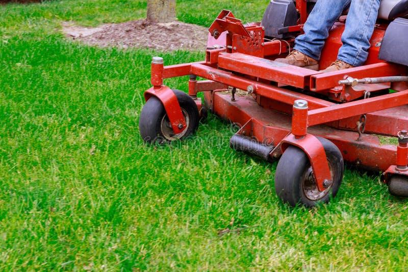 Lawn mower cutting green grass in backyard. Man lawnmower tractor, trimming, garden, gardening, work, mowing, tool, equipment, summer, care, machine, field royalty free stock photo
